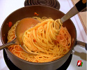 Position the spoon near the fork in the pan, continue to twirl the fork and slide the pasta onto spoon